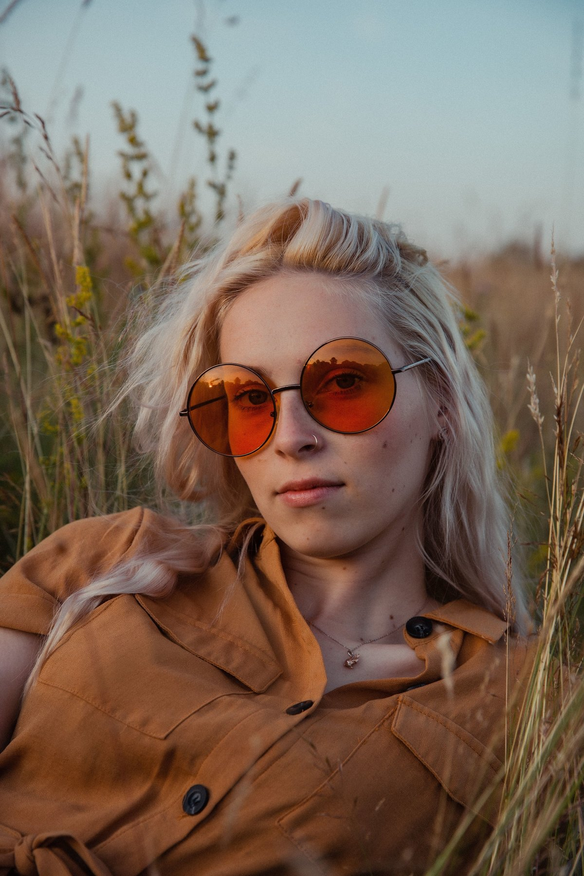 Amber sitting in the grass at golden hour, wearing orange sunglasses
