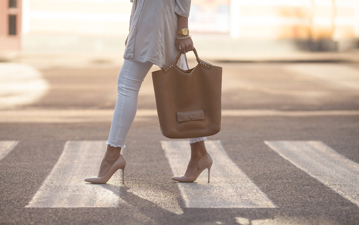 Woman wearing pumps and an oversized bag  in a crosswalk