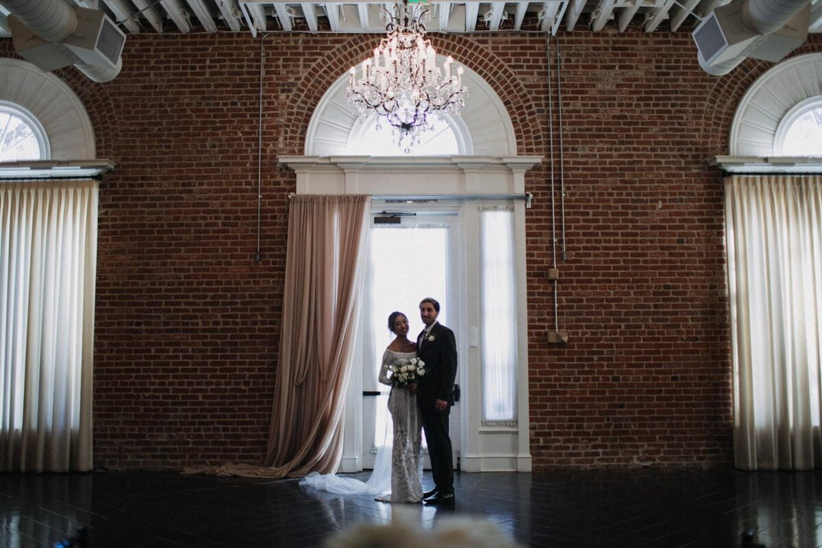 Bride-and-groom-stand-against-brick-wall-at-their-california-indoors-wedding