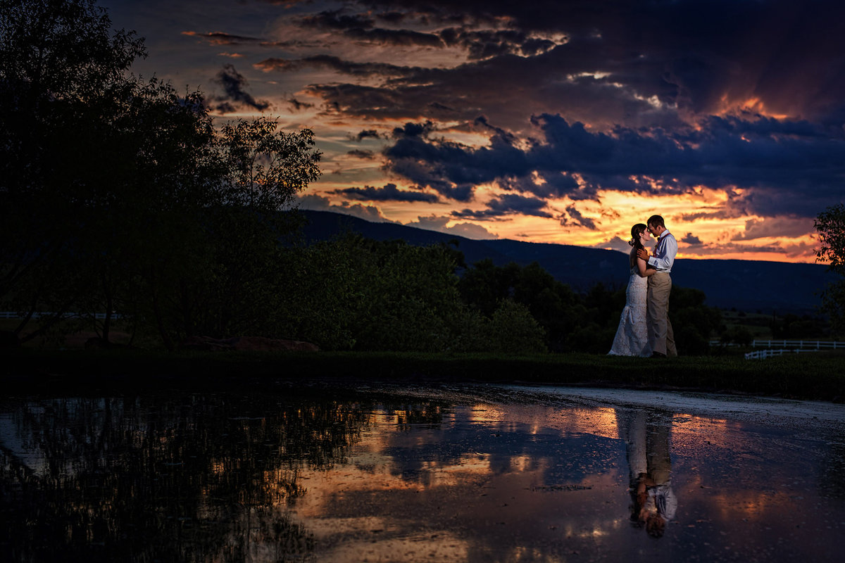 amazing sunset with bride and groom in lake