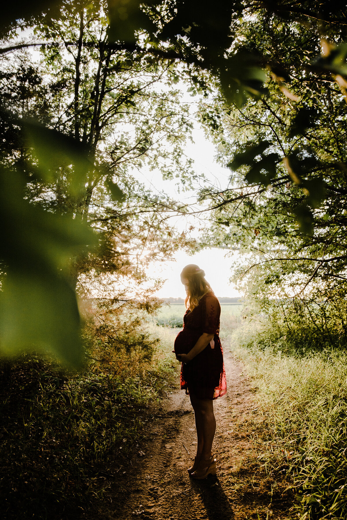 maternity session where mother is standing backlit in a field holding belly