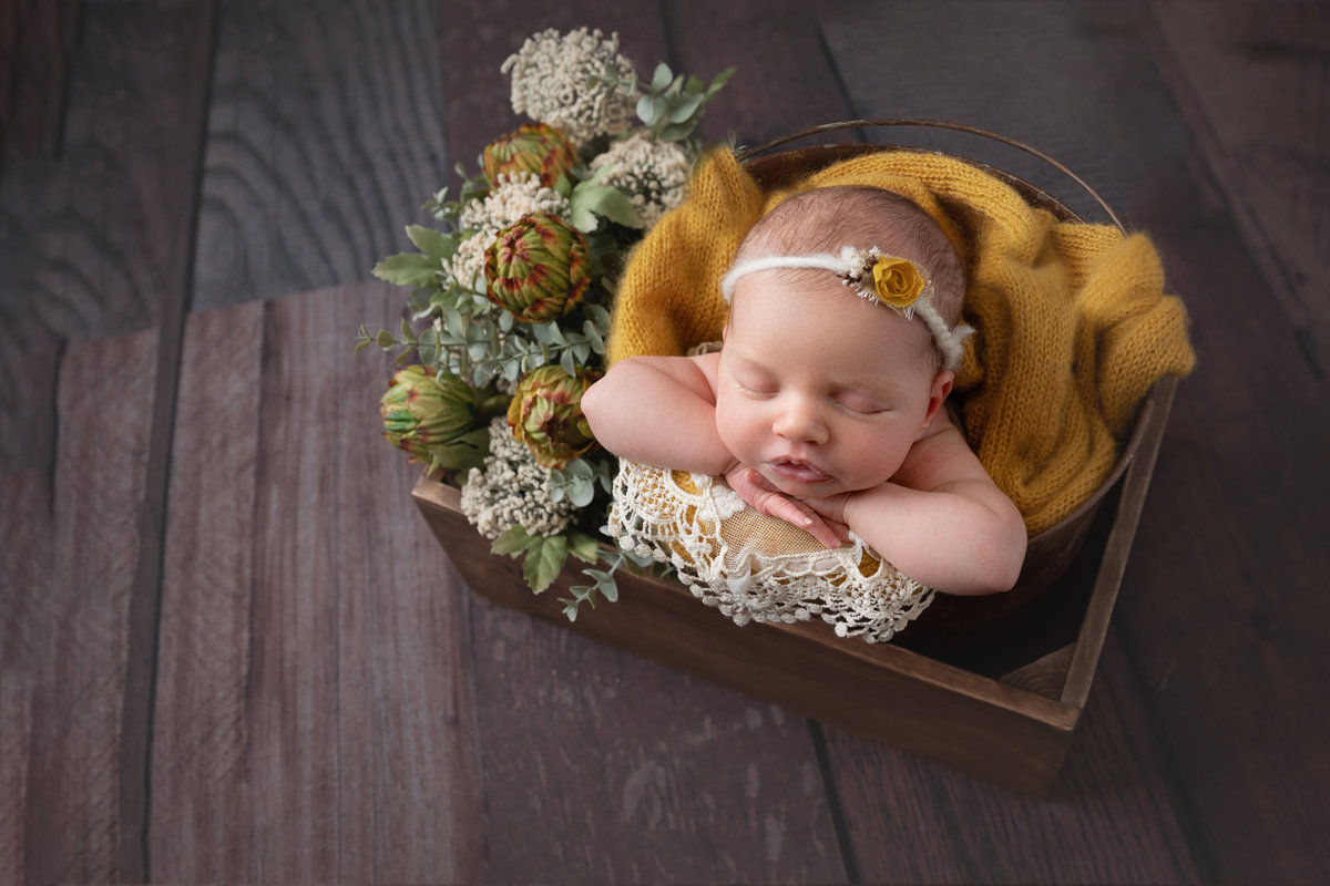 Little baby girl in a bucket with yellow accents