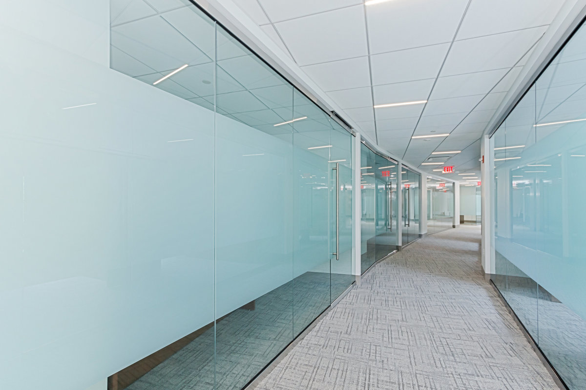 Hallway lined with glass doors leading to conference rooms.