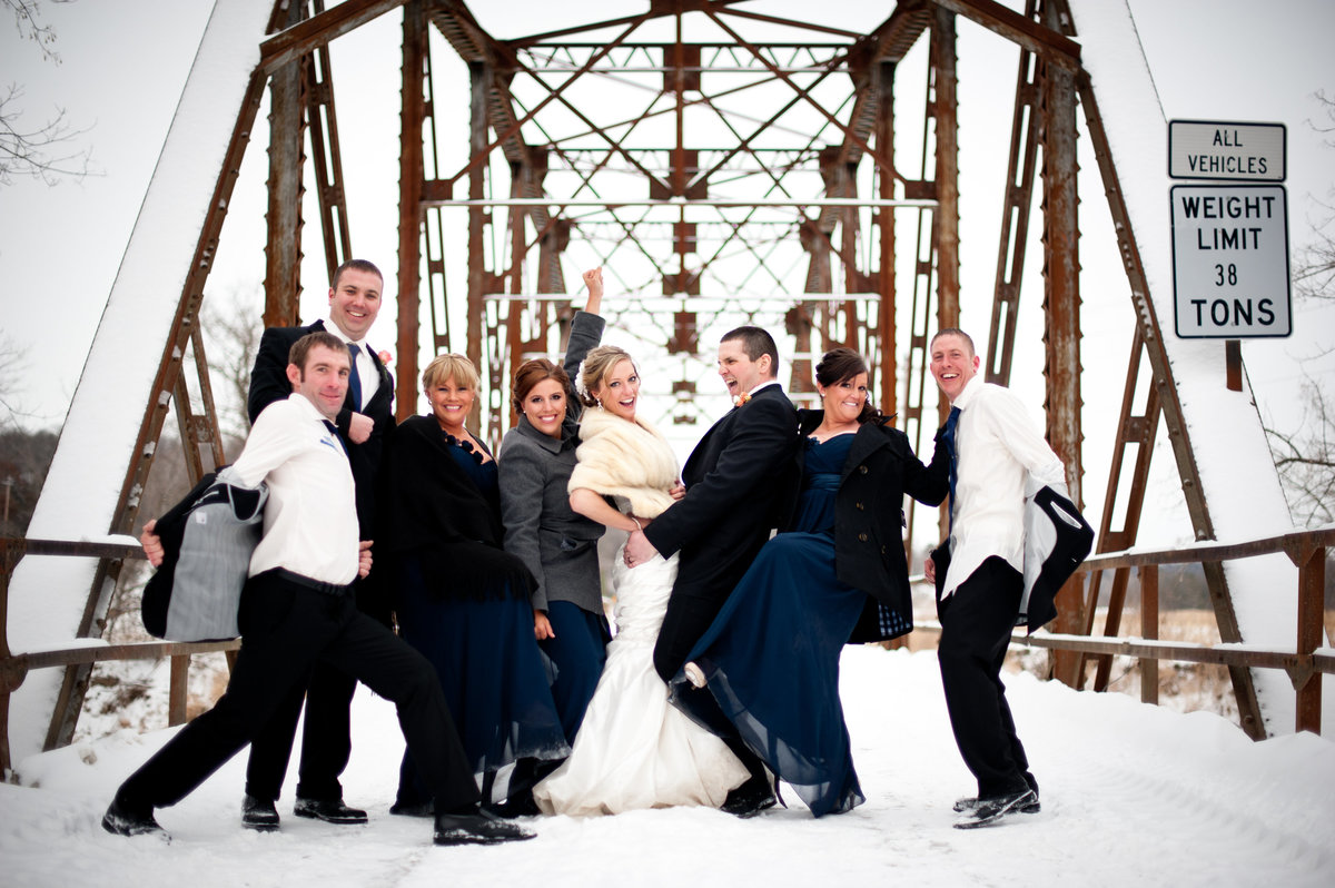 wedding party pose for a funny photo on bridge
