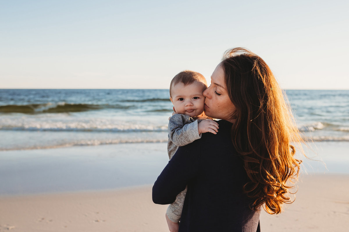 Mom kissing baby son, on beach