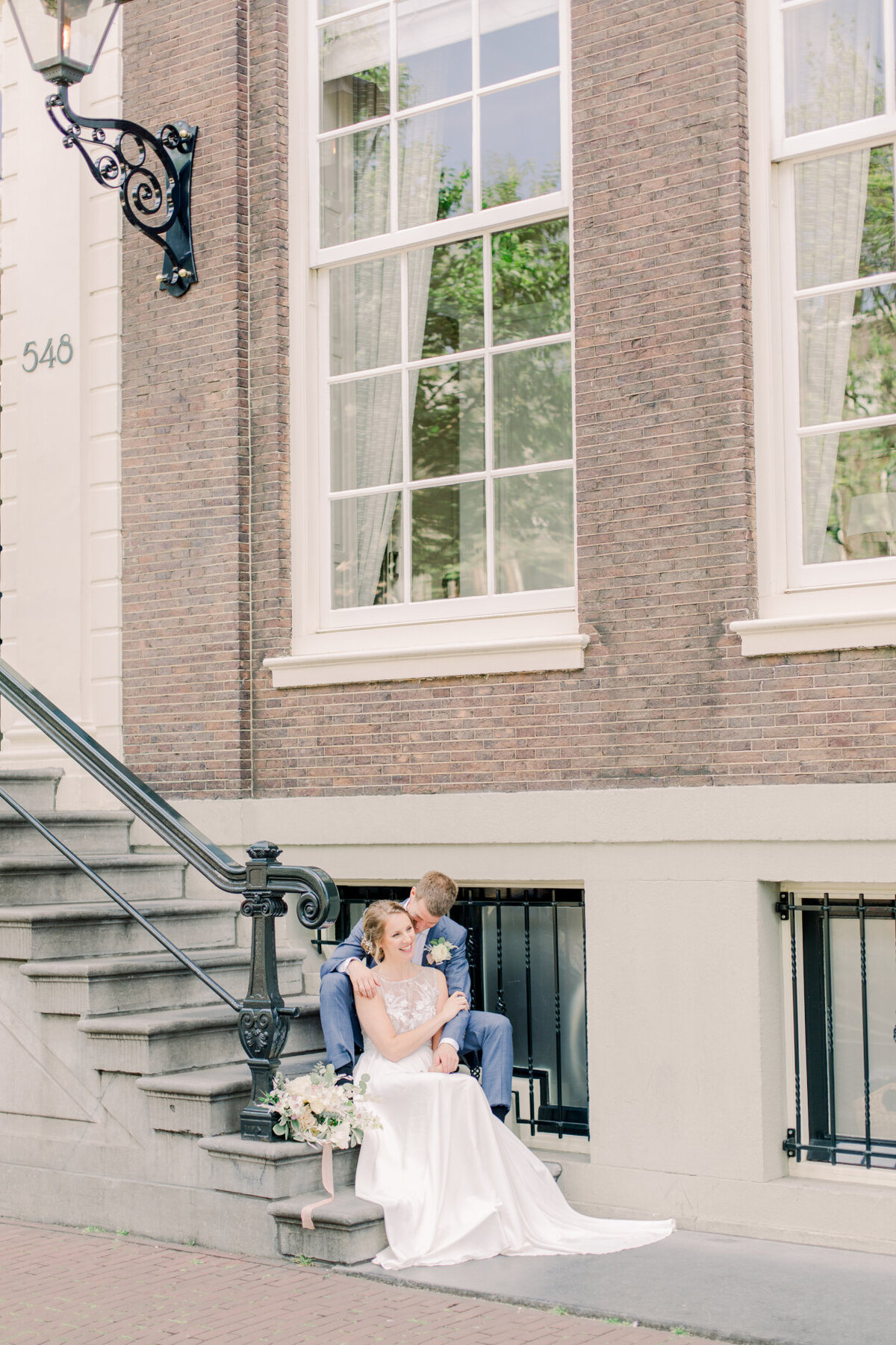 Wedding portrait of the bride and groom in the streets of Amsterdam for their city elopement for a photoshoot organized by Lovely & Planned