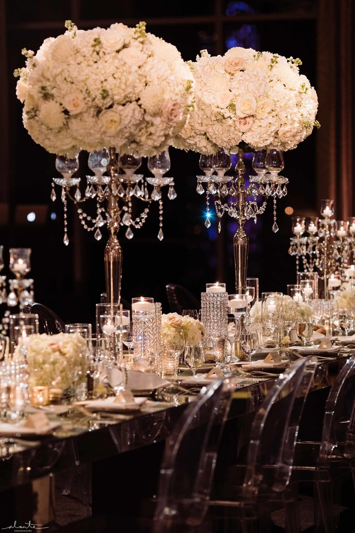 Flora Nova Design created these large white flower arrangements for a winter glam wedding head table with clear lucite chairs
