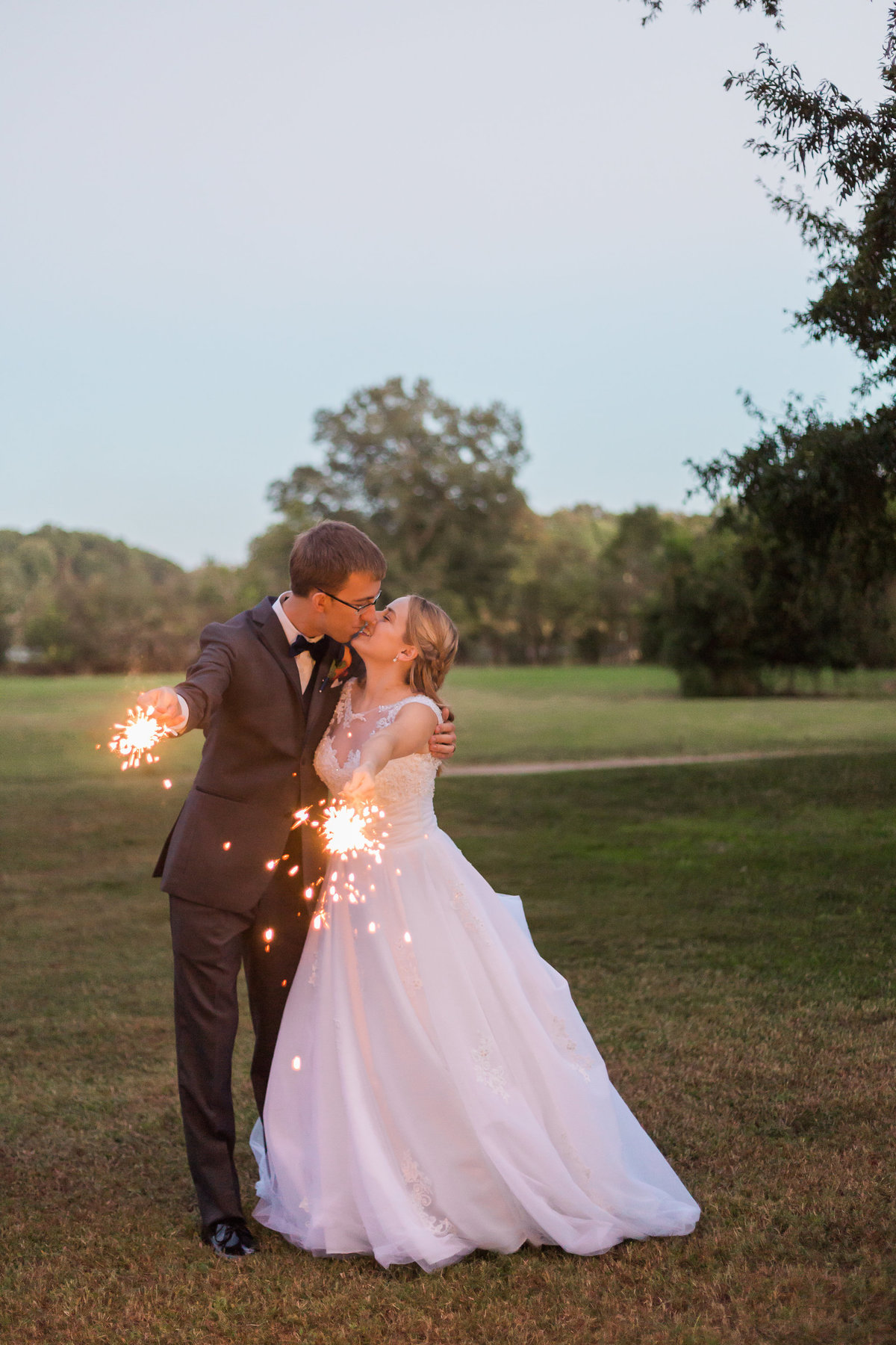 A bride and groom pose with sparklers at Fort Eustis