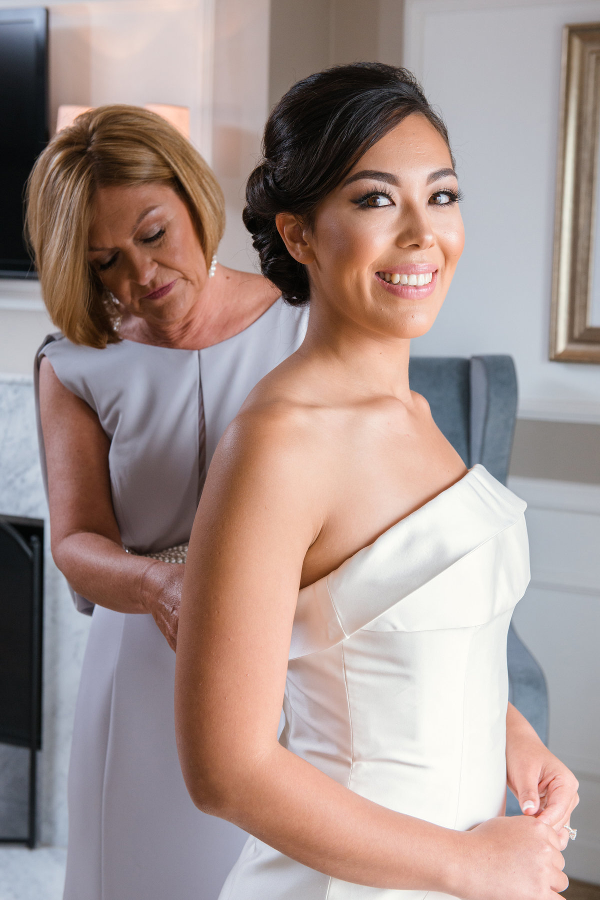 wedding photo of mom helping bride with dress at The Garden City Hotel