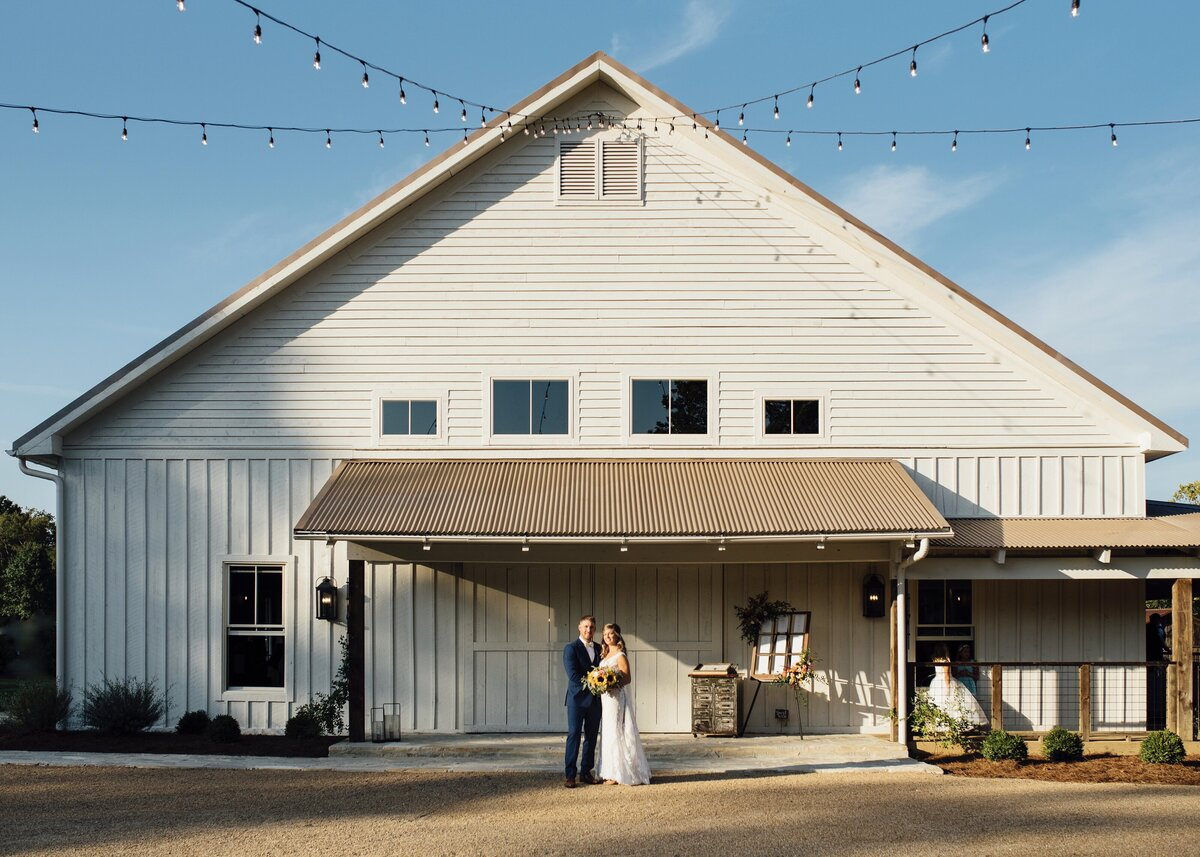 bride holds sunflower bouquet in front of rustic barn with patio lights overhead blue skies
