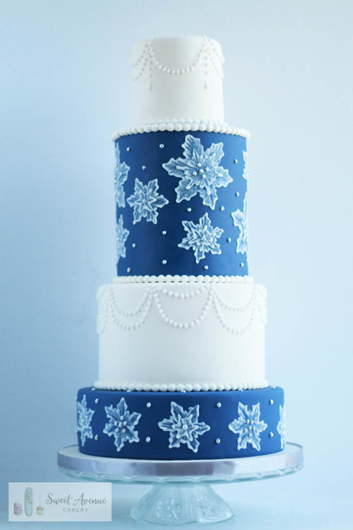 white and navy blue winter wedding cake with lace snowflakes