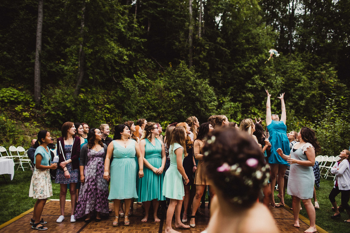 woman jumps high above everyone else to catch bouquet at backyard wedding