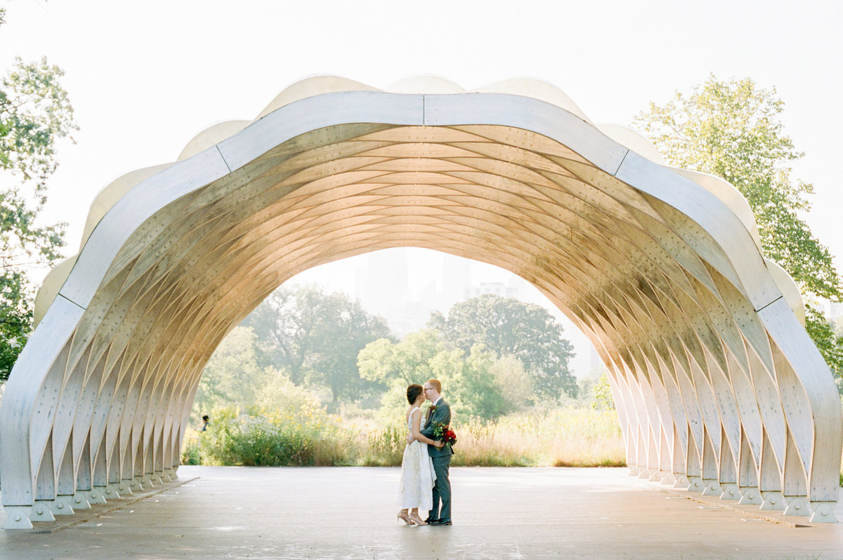 couple dancing under arch on sunny day