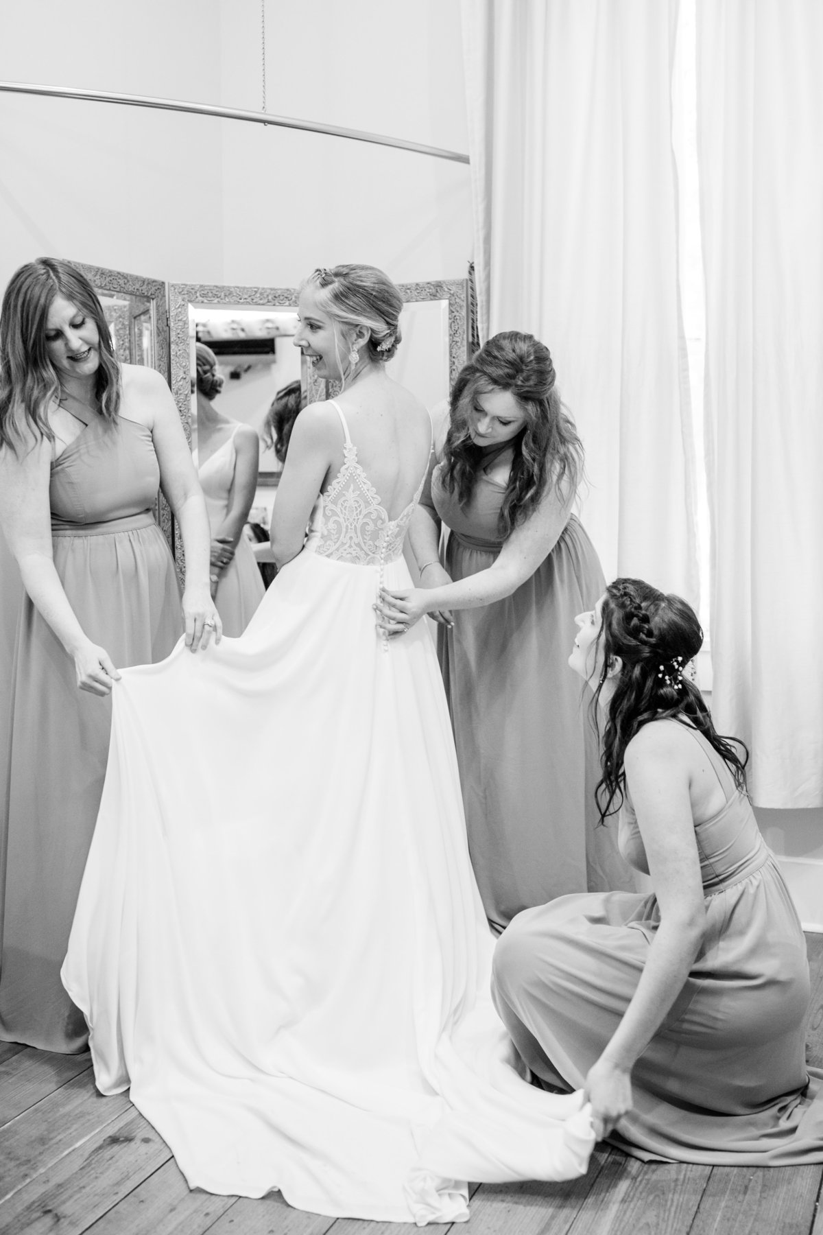 bride getting into dress with her  bridesmaids helping