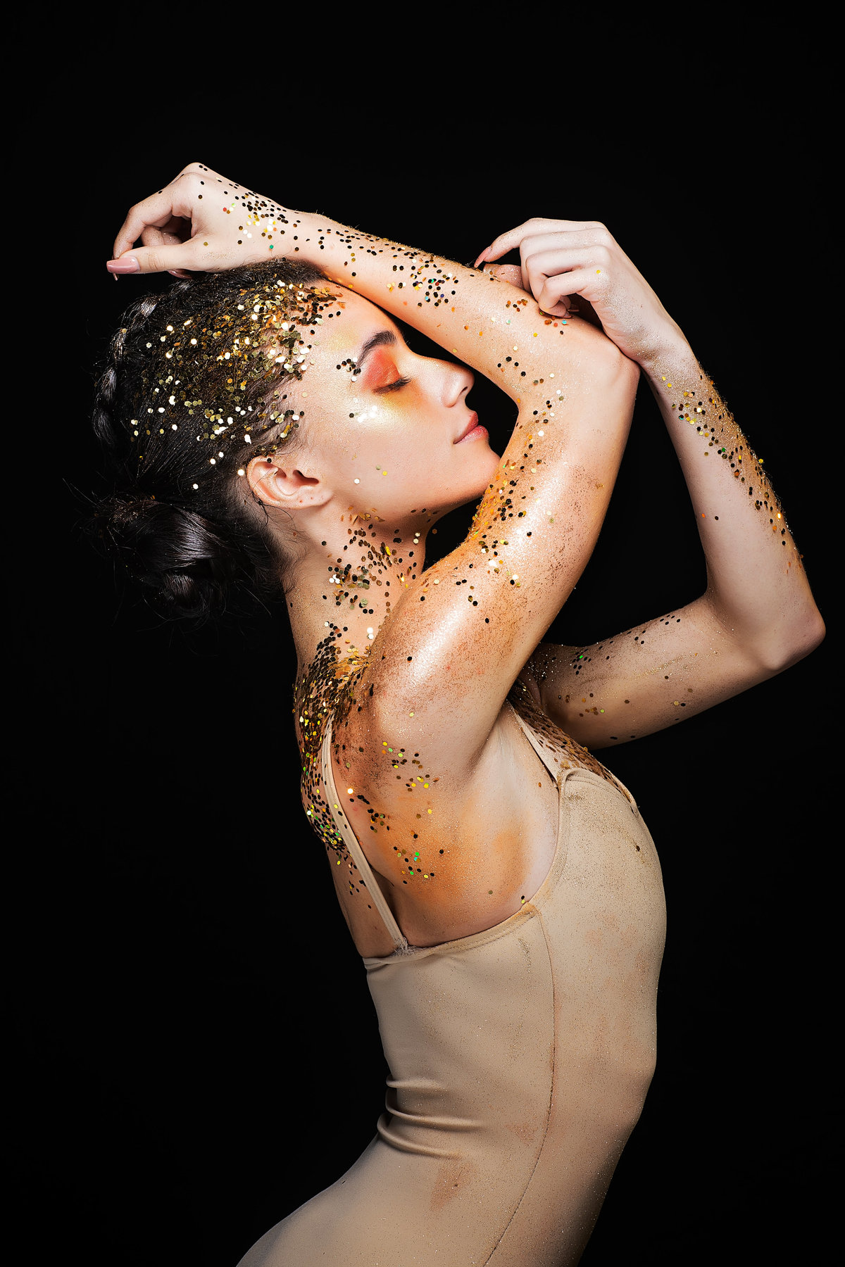 dancer covered in gold glitter in pose