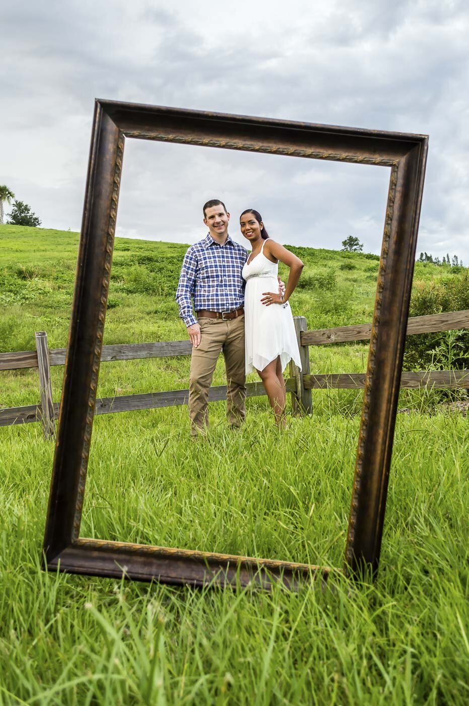 Engaged couple poses framed by a large wooden frame