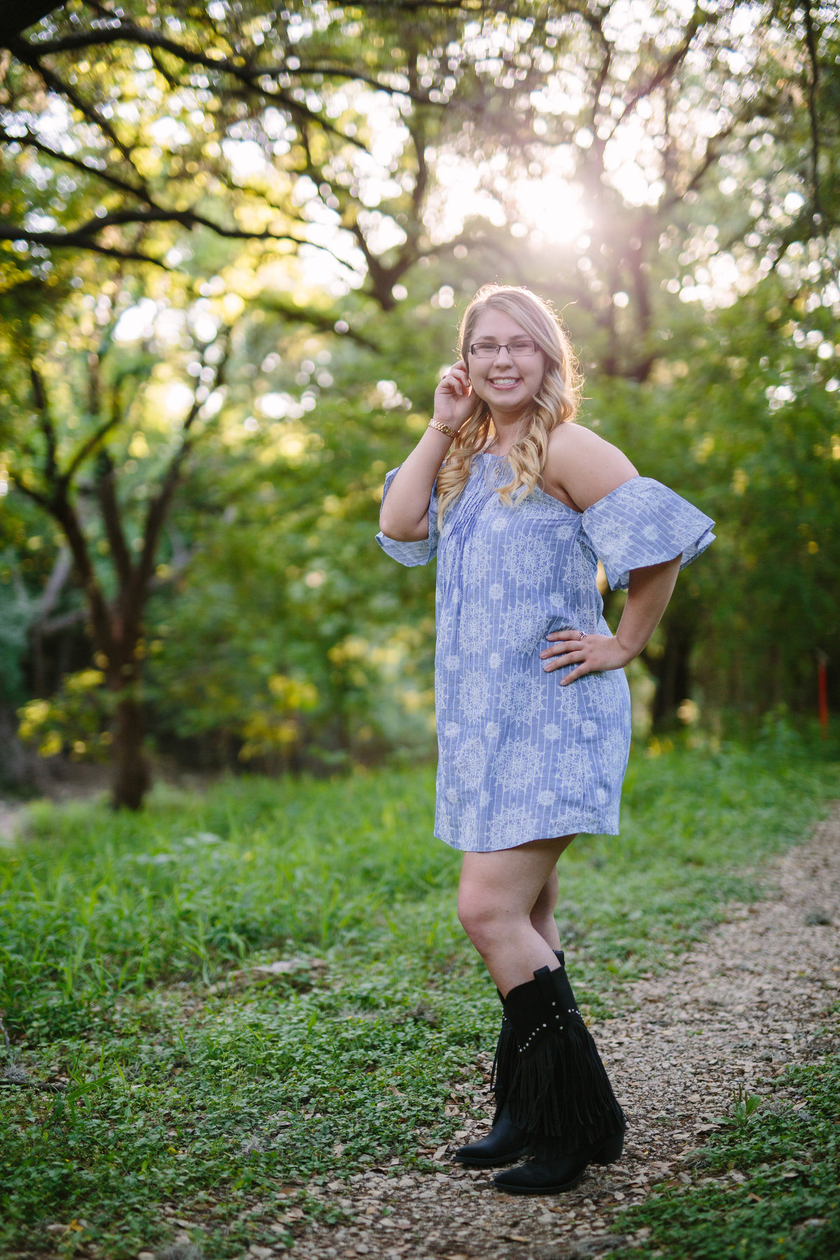 high school girl posing wearing boots for session by San Antonio high school senior photographer