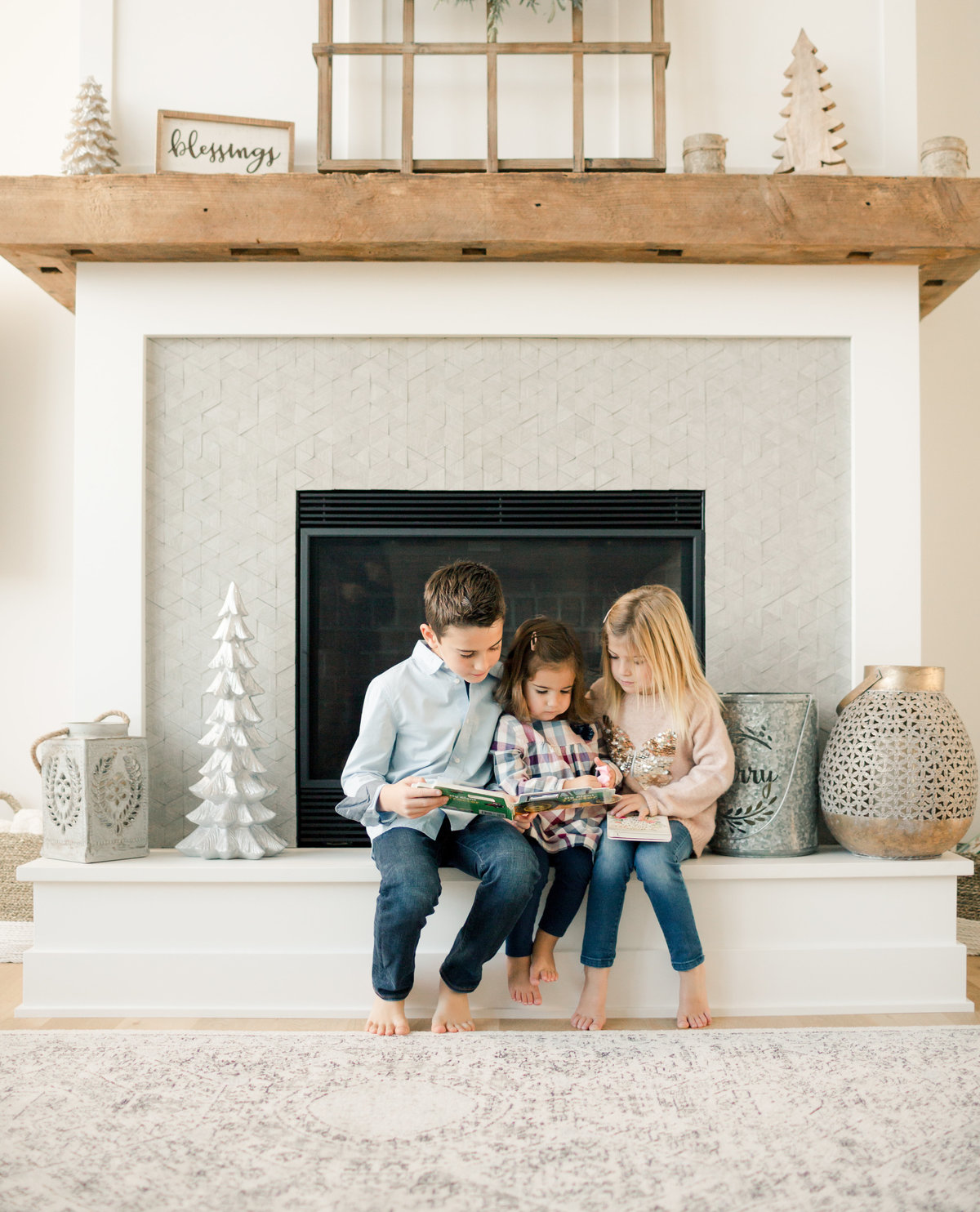 siblings read book to two year old sister in front of fireplace