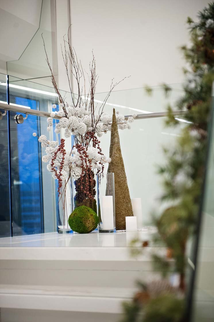 holiday decor for office stairway with tall cones, moss ball, flocked branches, and hurricane candle