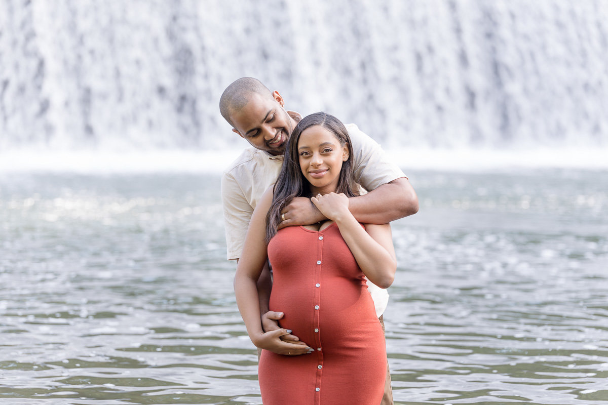 Husband cradles wife's pregnant belly in red dress maternity photo session