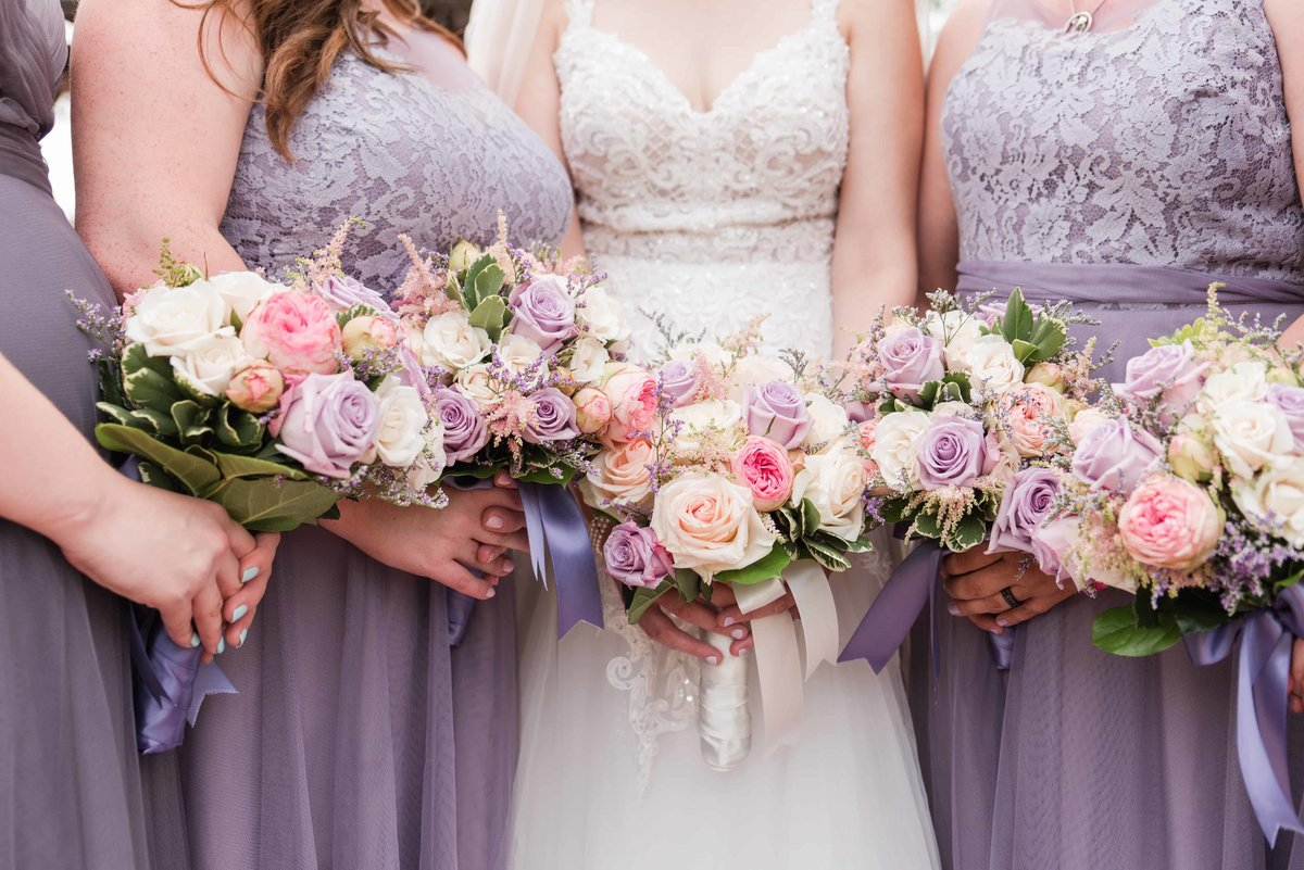 Bride with her bridesmaids showing off their wedding flowers.