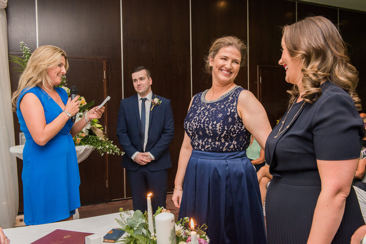 Gay brides wearing navy wedding dresses at ceremony in hotel