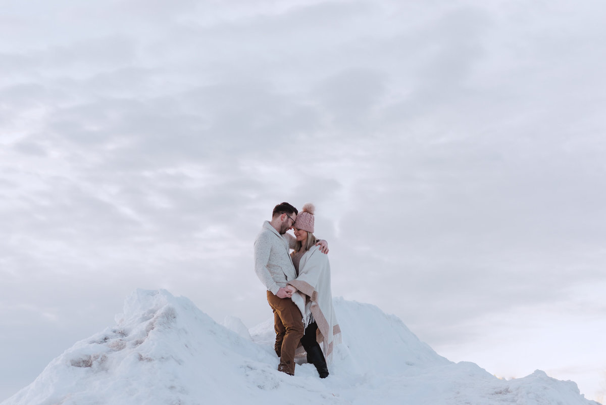 engaged couple at the top of a snowy mountain at sunset
