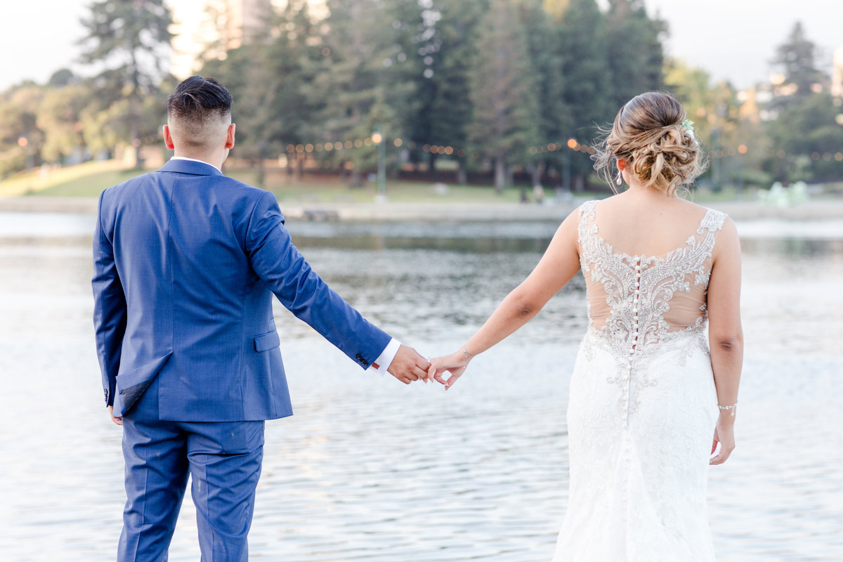 Bride and groom hold hands looking out over Lake Merritt in the Bay Area