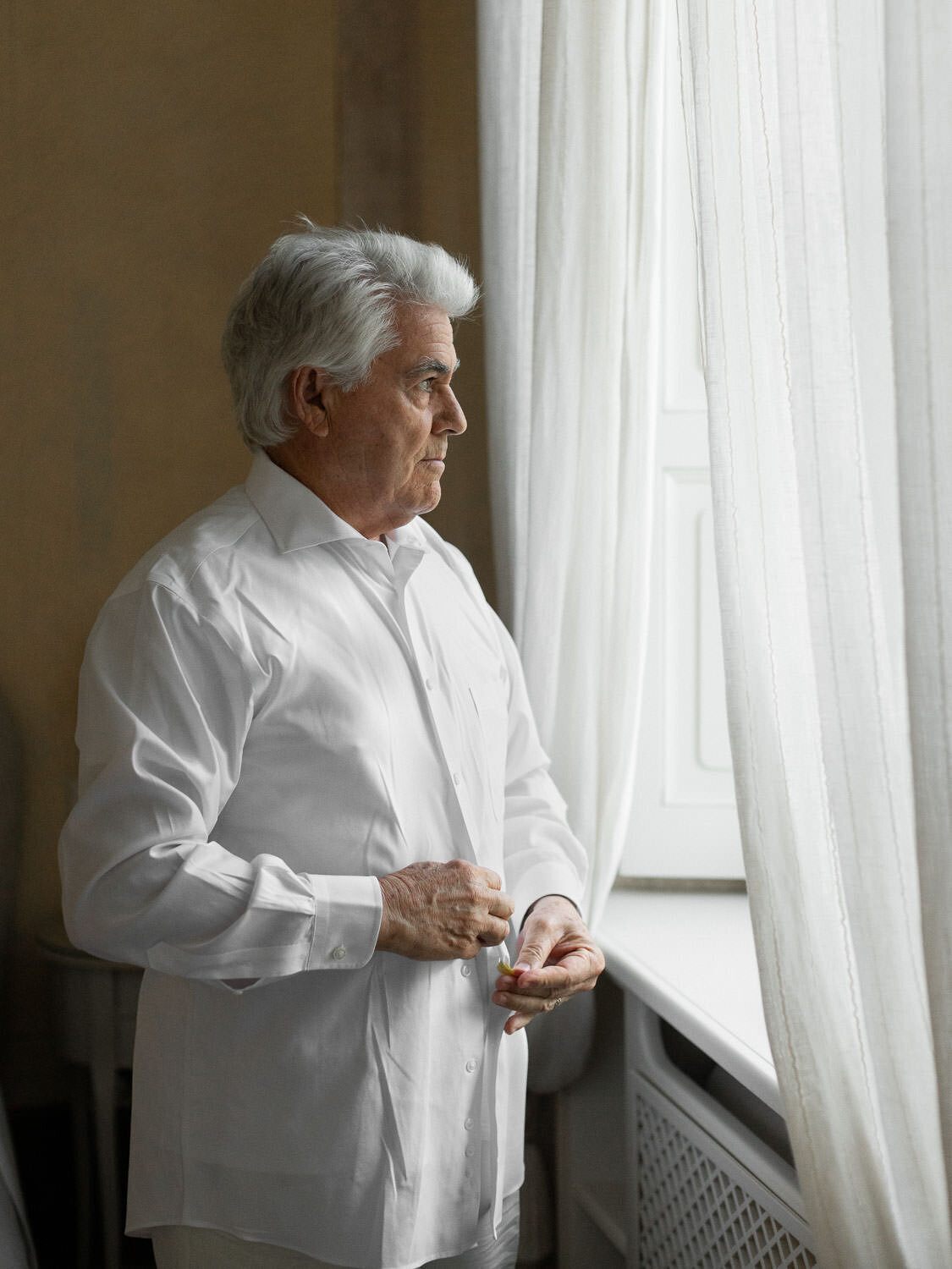 grey headed father buttoning white shirt in front of window