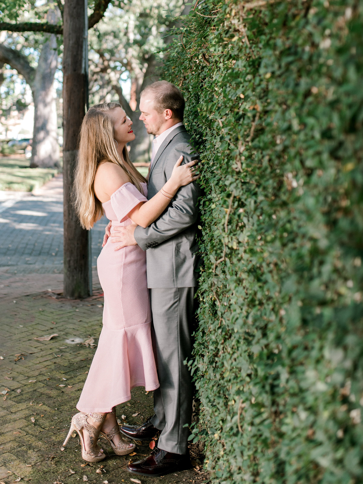 Couple leans against Ivy wall
