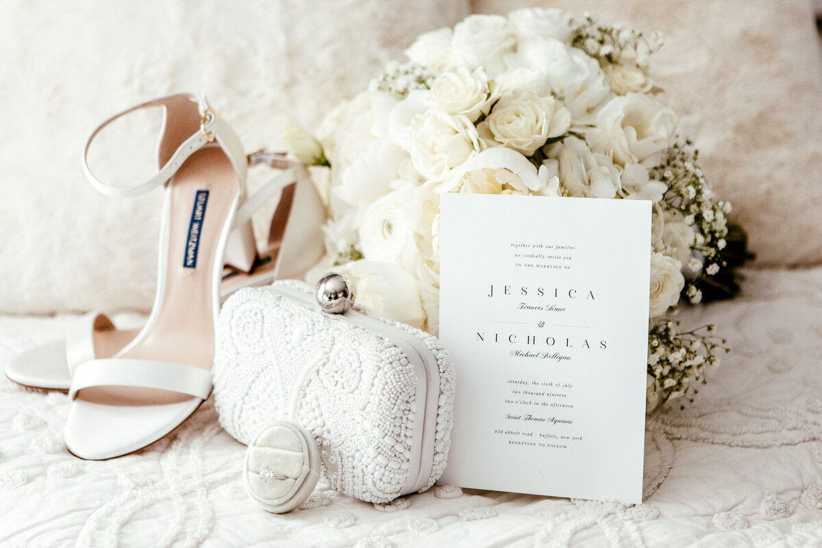 Wedding invitation against bouquet of white roses and among white heels, lace clutch bag and wedding ring