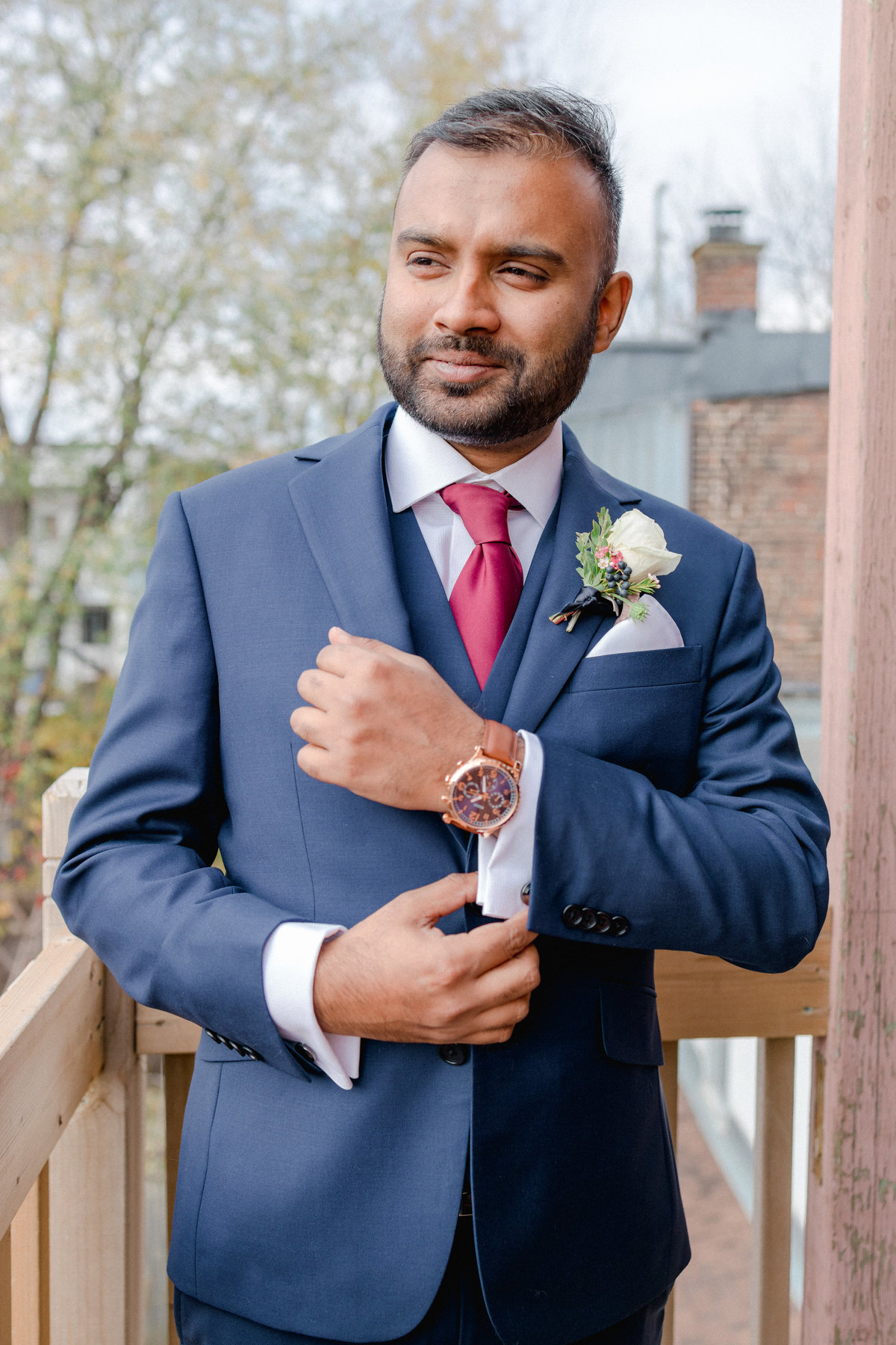 Groom outside on balcony in Montreal showing off his suit, watch, and cufflinks