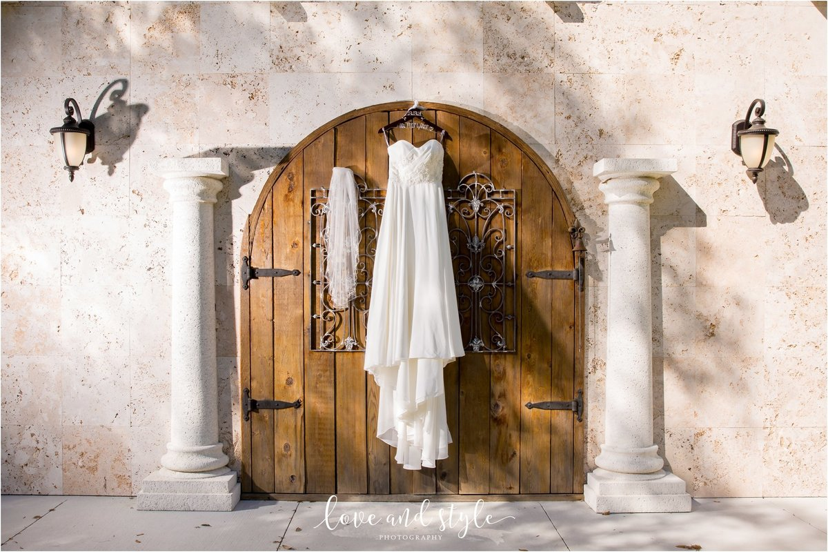Bakers Ranch Wedding Photography of the wedding dress hanging on the wooden doors