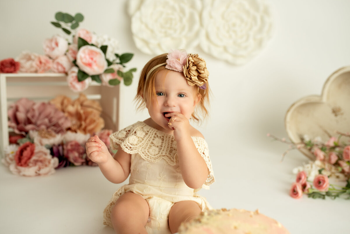 girl eating her first birthday cake