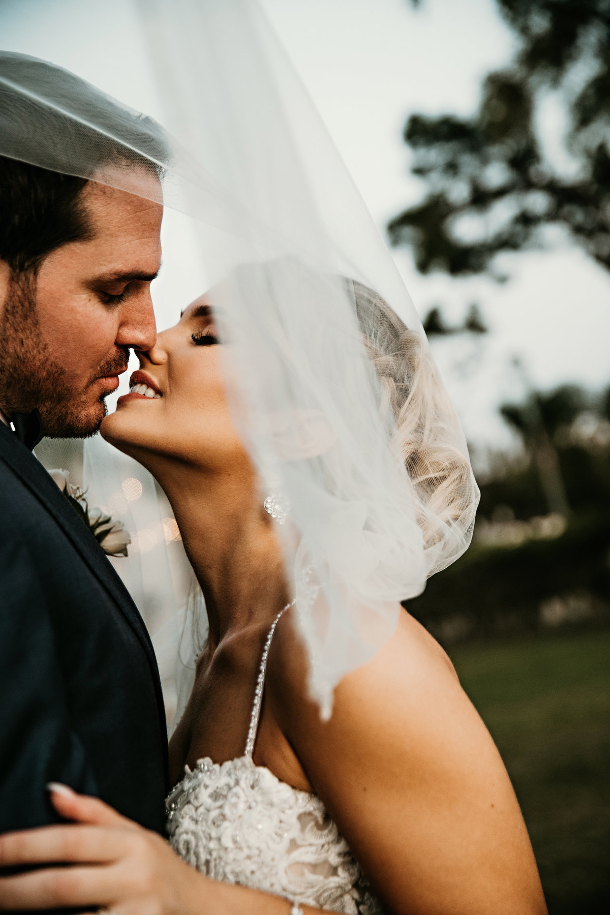 An image of a closeup view of the bride and groom romantically leaning in to kiss as the bride's veil drapes around them by Garry & Stacy Photography Co - Tampa wedding photographers