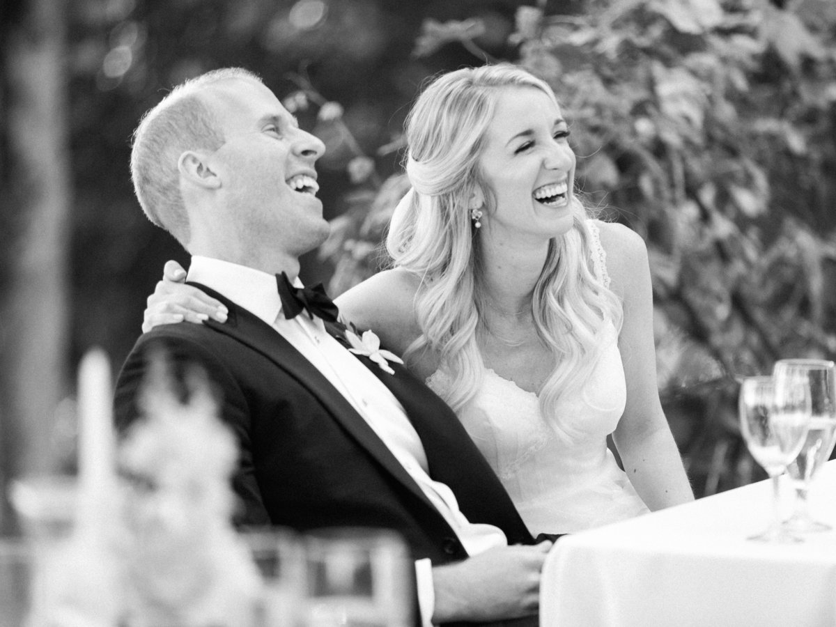 bride and groom laughing during wedding toasts