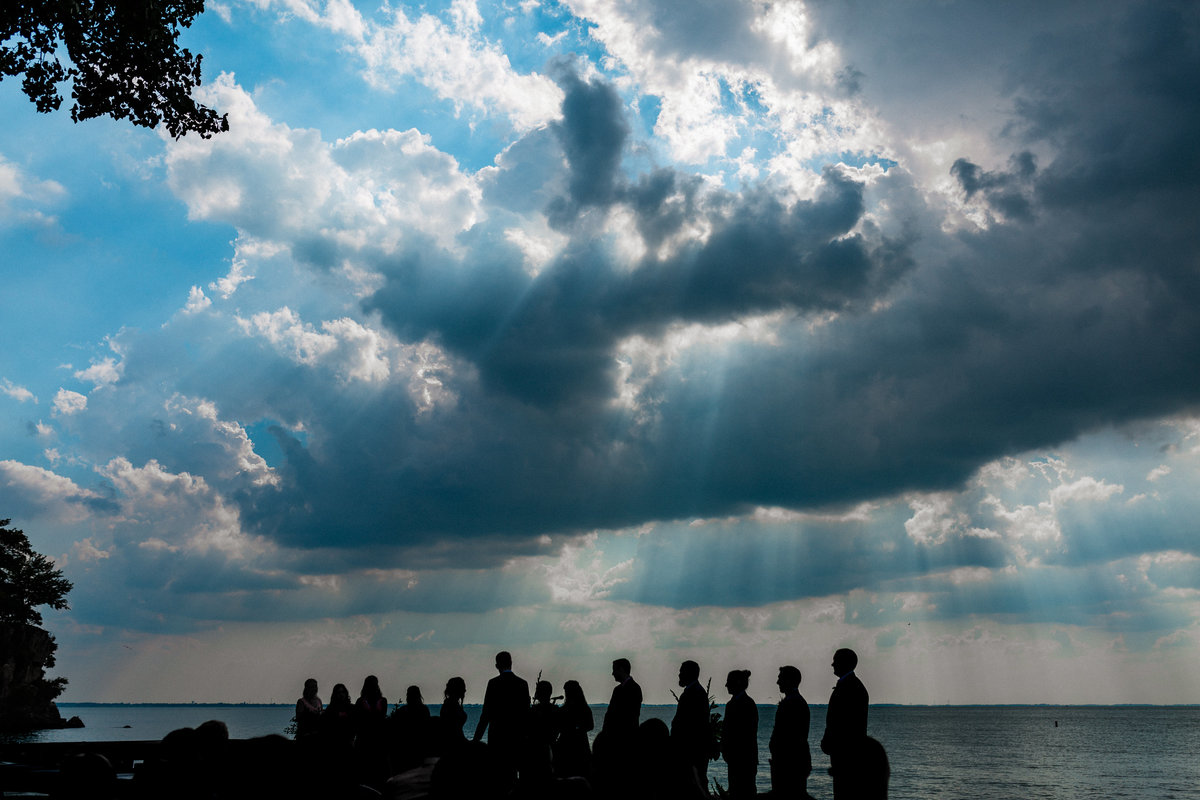 A ceremony taking place on the waterfront of lake Erie as beautiful clouds and sun shine down from above