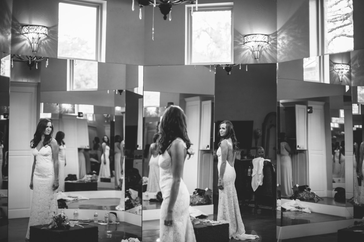 Bride looking at herself in mirror prior to wedding ceremony as she gets ready at Remi's Ridge at Hidden Falls