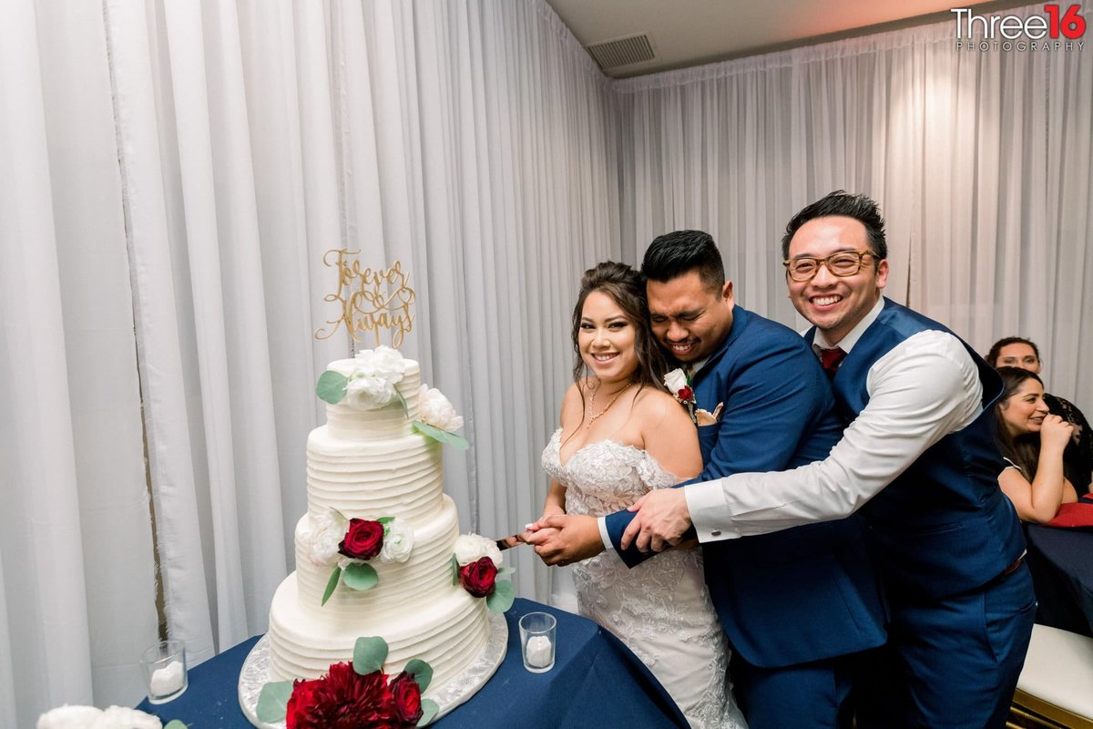 Bride and Groom get a little help from groomsman for cake cutting ceremony