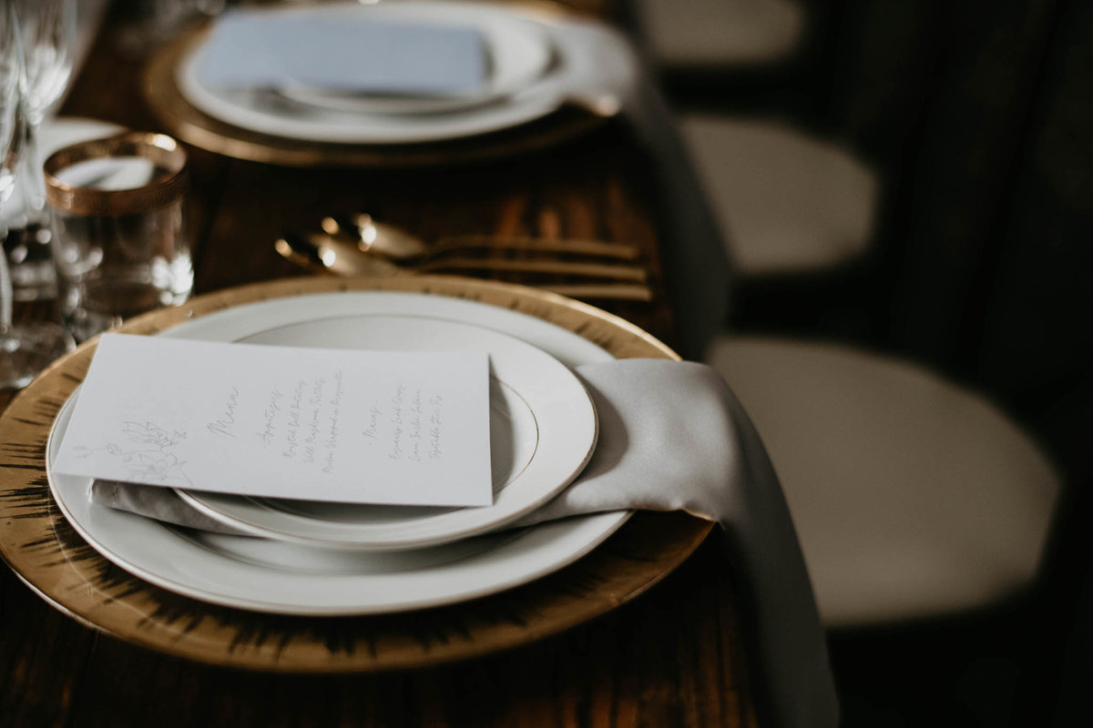 gold plates, white china and grey napkins on harvest table