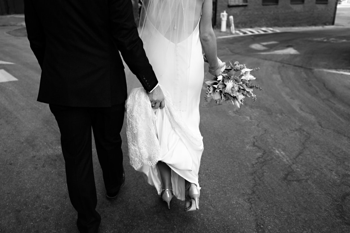 The groom holds the bride's dress as they make their way downtown Portland Maine on their wedding day
