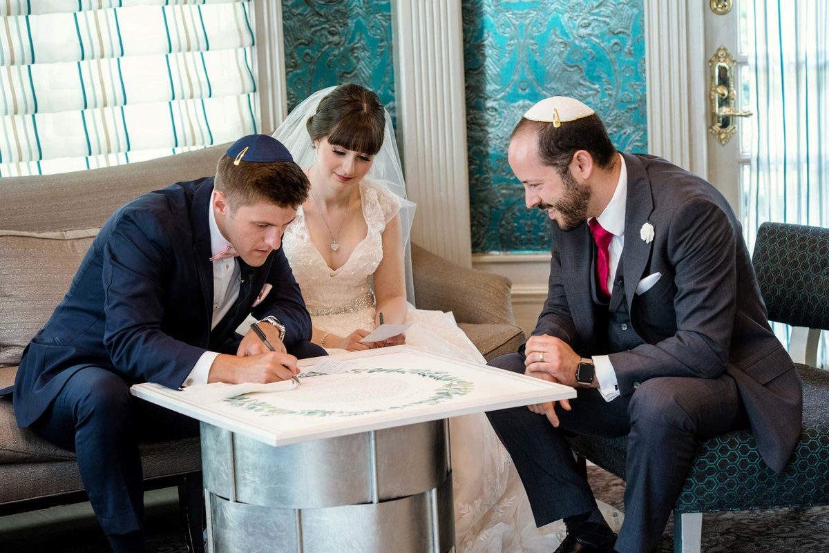 Fox Hollow Jewish wedding ceremony, bride and groom signing the ketubah
