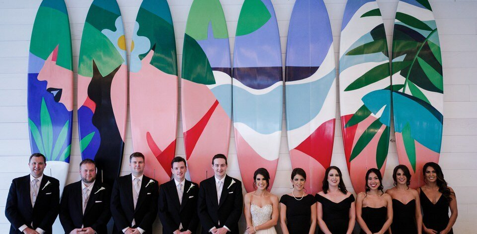 wedding party poses by the surfboard art installation
