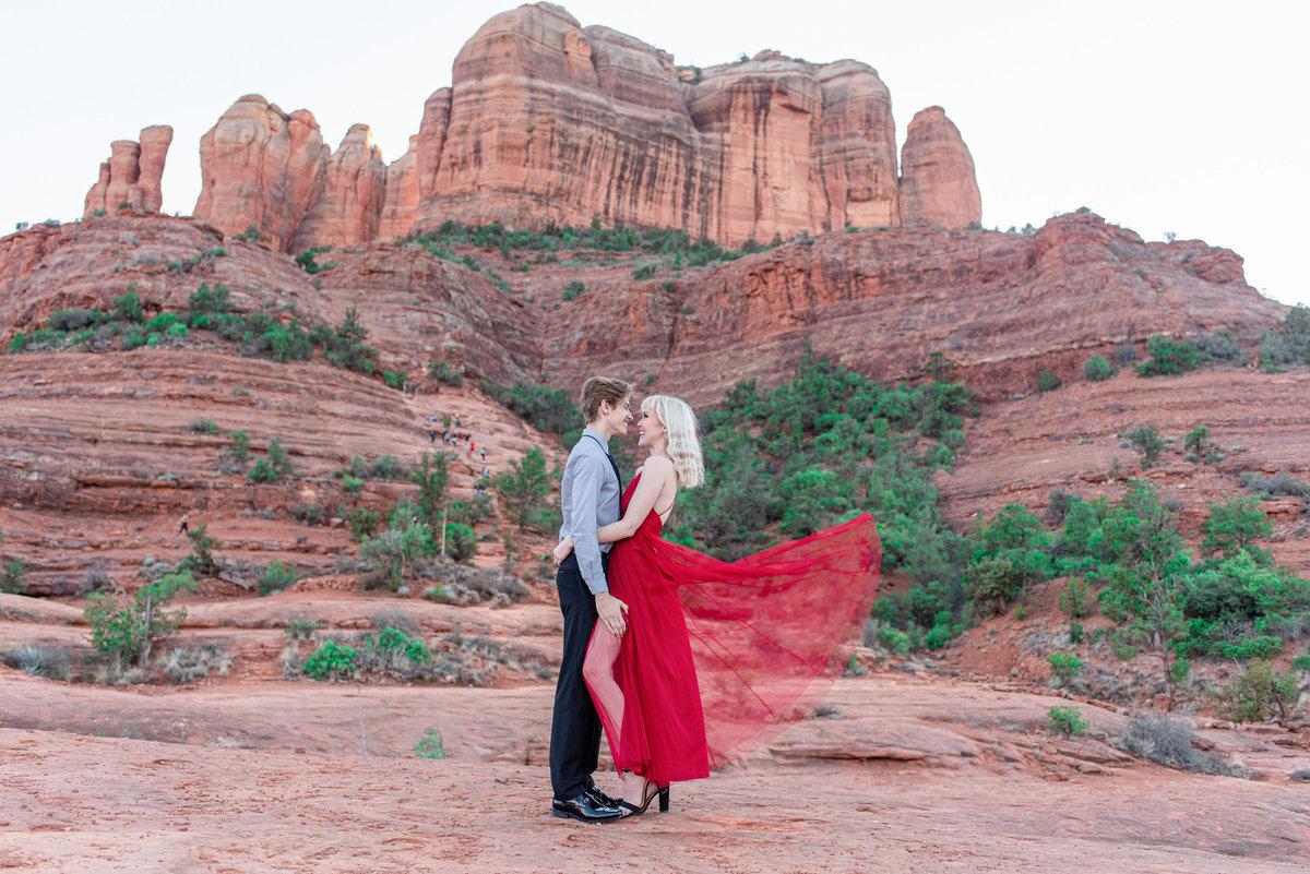 couple hugs in front of cathedral rock in sedona while her red dress flows behind her