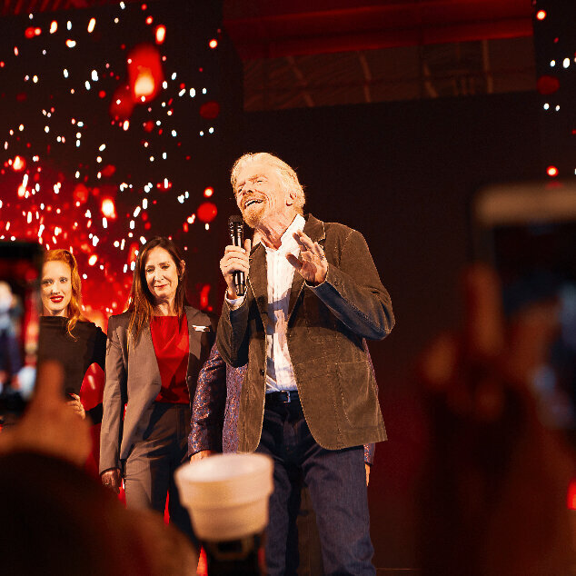 Richard Branson making a speech at a party for Virgin Voyages in London with a red video screen.