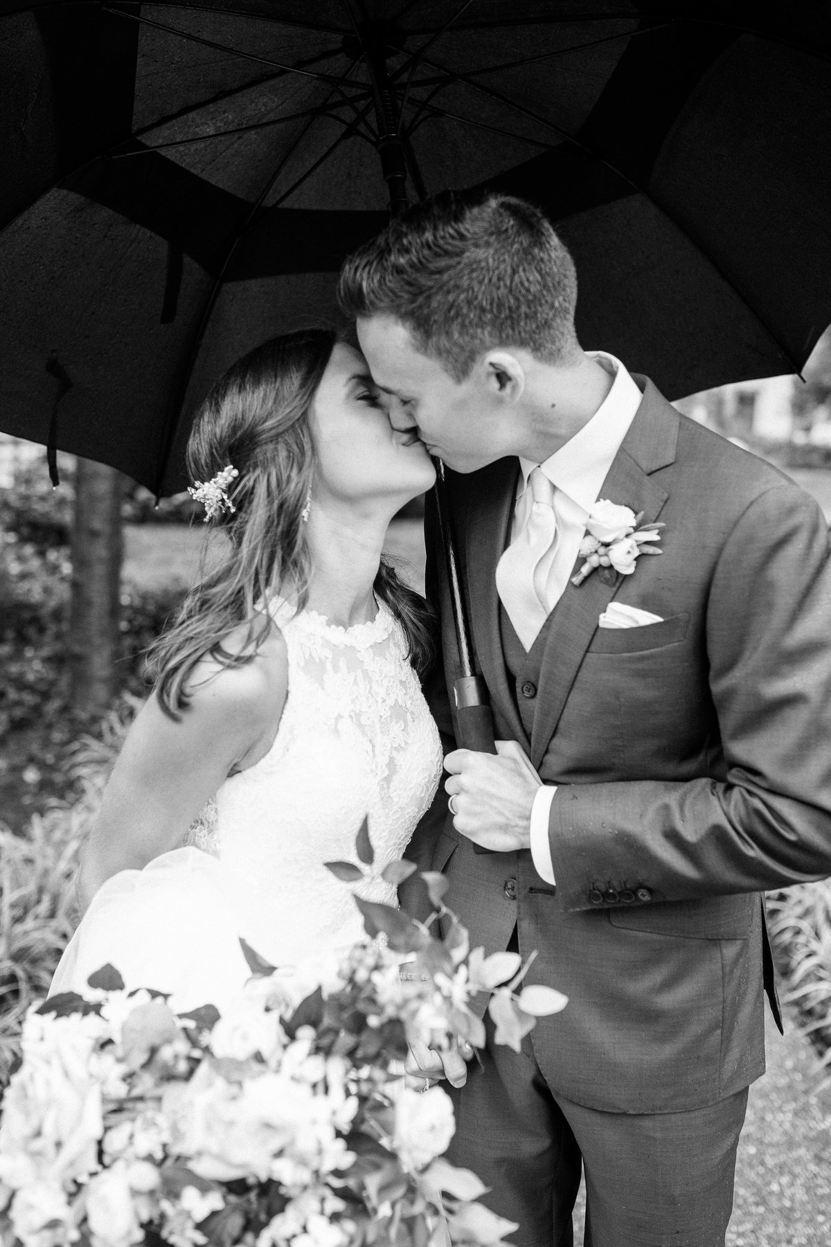 A bride and groom kiss under an umbrella on their rainy wedding day