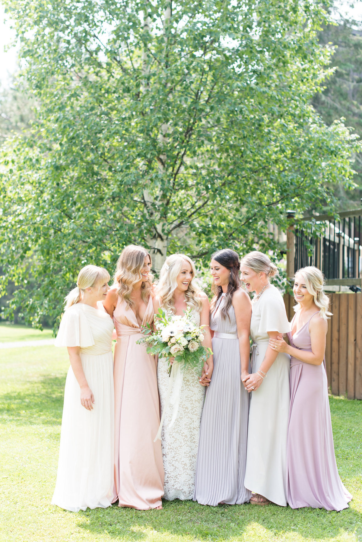 Bride and her bridesmaids in colour coordinated dresses before her wedding at Stepstone Centre in Thunder Bay