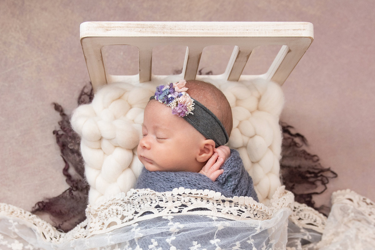 newborn baby girl in baby bed prop