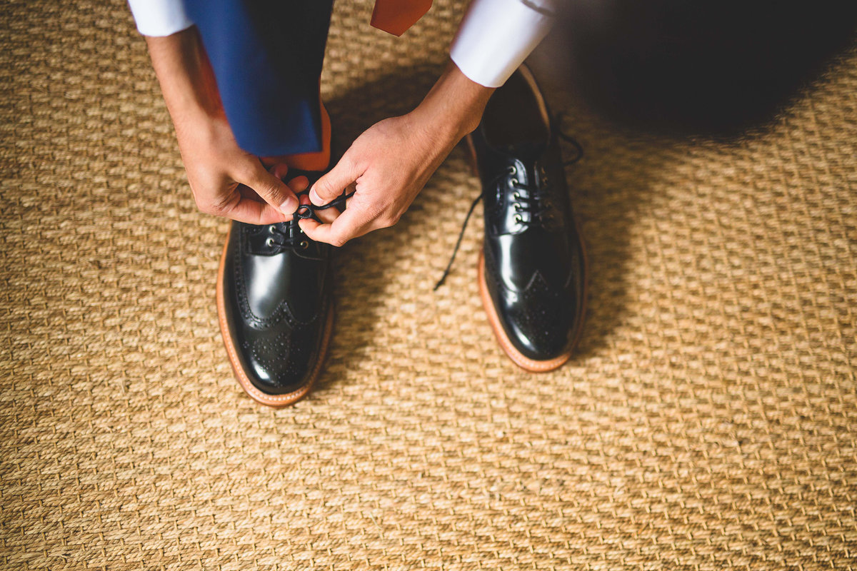 detail photo of groom tying shoes