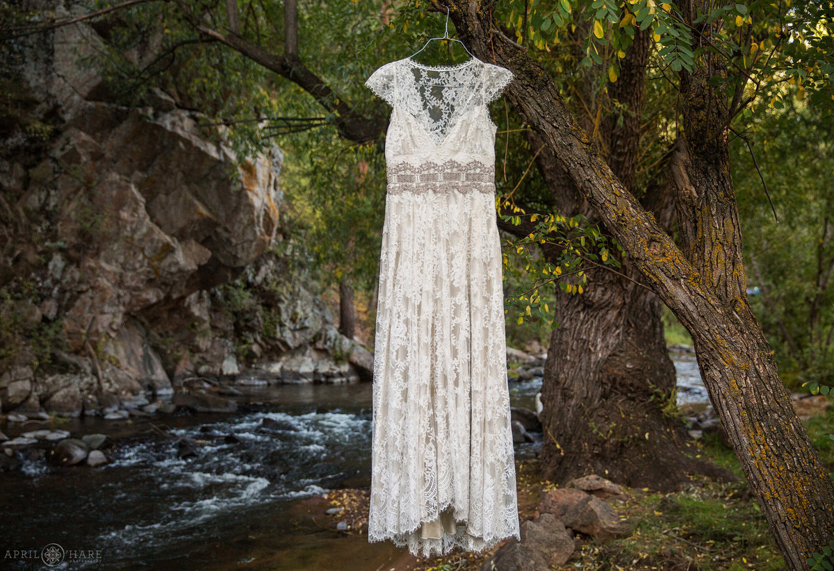 Evergreen Colorado Wedding photographer lace bohemian wedding gown hangs creekside at Bear Creek Cabins